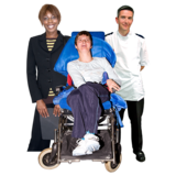 a photograph of a person in a wheel chair surrounded by two people who appear to be staff